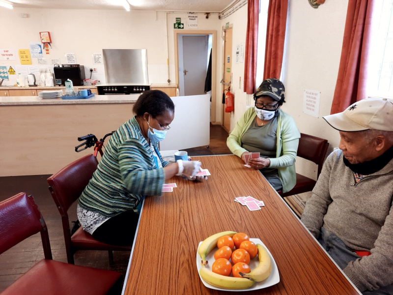 """The older person is fully absorbed with his card activity he calls """"PATIENCE """" and another is counting as she gives them out."""