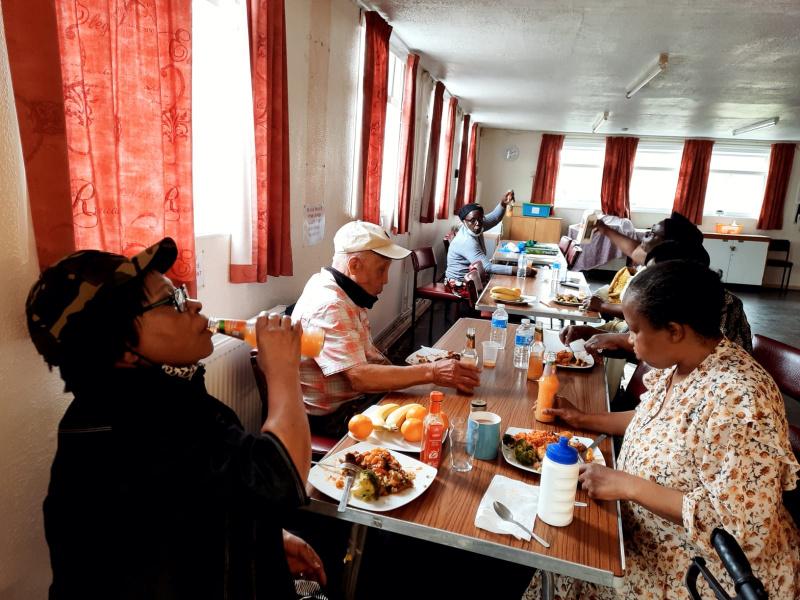 """Older persons enjoying a dish from Uganda  called """" katogo kammatooke ne nyama"""" with fruity drinks."""