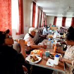 """Below is another cooking session by another older person and her favorite dish from Uganda  called """" katogo kammatooke ne nyama"""".  Older people loved it as you can see. In the picture.enjoying  it with fruity drinks."""