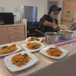 "Older person serving ""Gambian Jollof rice """
