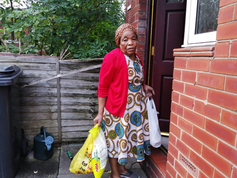 Eldery lady in Bury receiving her parcel of cultural foods and hoe essential items.