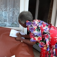 Elderly lady signing to acknowledge receipt of her parcel from OBADO